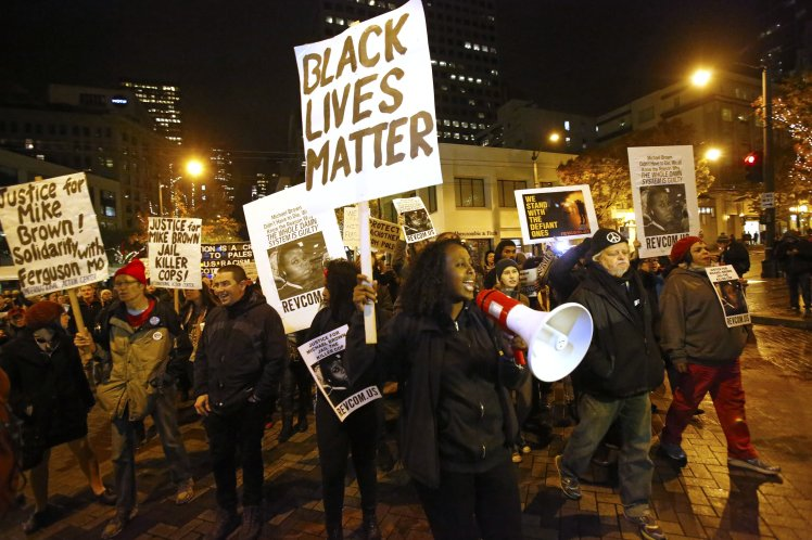 Seattle activists protest against the grand jury's decision not to indict Darren Wilson, the policeman who shot Michael Brown to death.