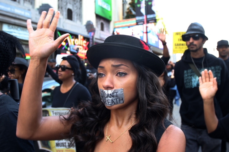 "A Los Angeles activist with her mouth taped over in memory of Eric Garner's last words ""I can't breathe"" repeated eleven times as he was choked to death by policeman Daniel Pantaleo."